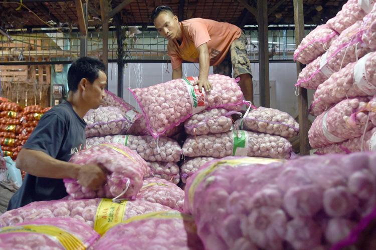 Pedagang menata tumpukan karung bawang putih impor