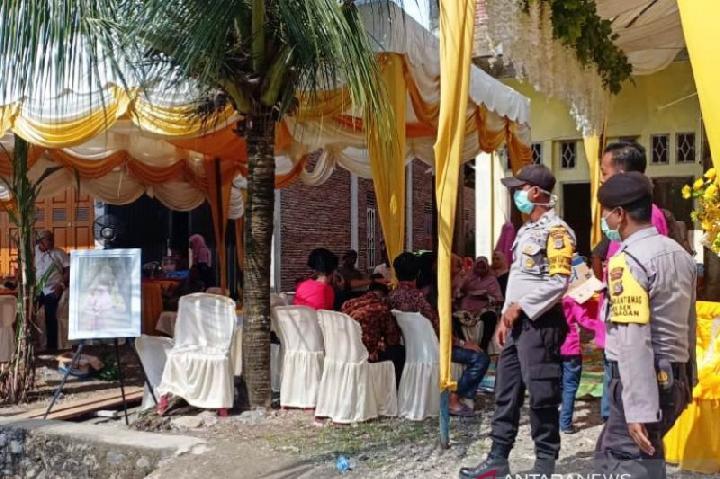 etugas kepolisian bersama tim gabungan terdiri dari TNI dan polisi syariah, berusaha membubarkan sebuah resepsi pesta pernikahan di kawasan Desa Cot Peuradi, Kecamatan Suka Makmue, Kabupaten Nagan Raya, Provinsi Aceh, untuk mencegah paparan virus corona (COVID-19), Senin, 30 Maret 2020. (Dokumen Polres Nagan Raya Aceh)