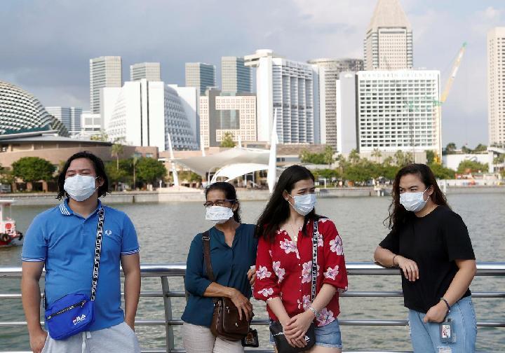 Turis memakai masker wajah di Merlion Park di Singapura, 28 Januari 2020. [REUTERS / Feline Lim]