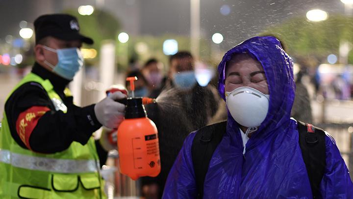 eorang petugas polisi menyemprotkan desinfektan pada seorang warga yang ingin berpergian meninggalkan Wuhan di luar Stasiun Kereta Api Hankou di ibukota provinsi Hubei, China, 8 April 2020. Ribuan orang bergegas meninggalkan Wuhan setelah otoritas setempat mencabut larangan warga berpergian selama lebih dari dua bulan di kota yang merupakan asal muasal pandemi virus corona (Covid-19) itu. REUTERS