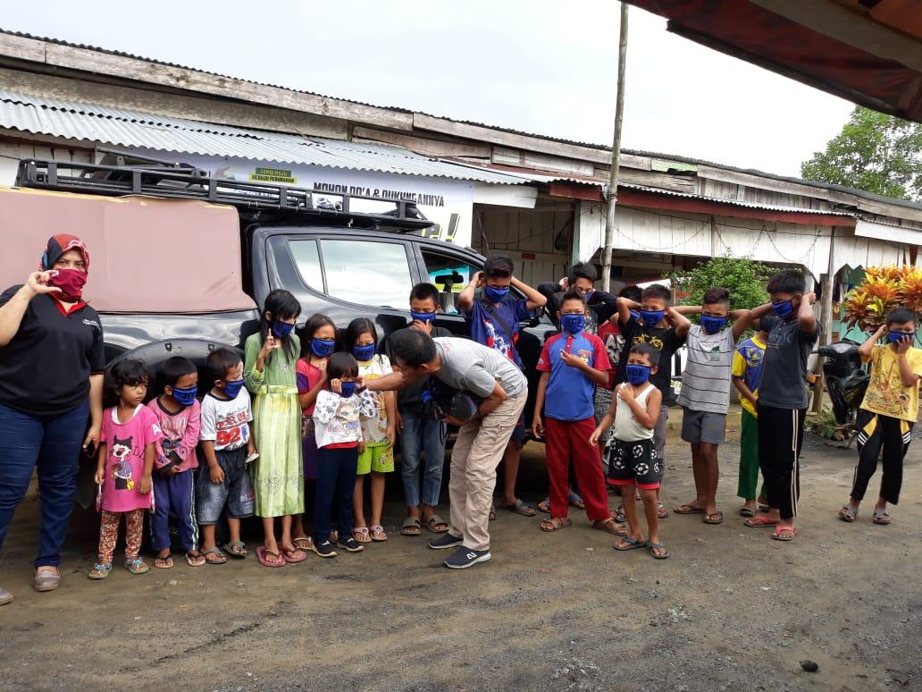Anak-anak itu awalnya berkerumun tanpa masker. Mereka bergegas menyambut masker gratis dari Cek Endra dan langsung dikenakan.
