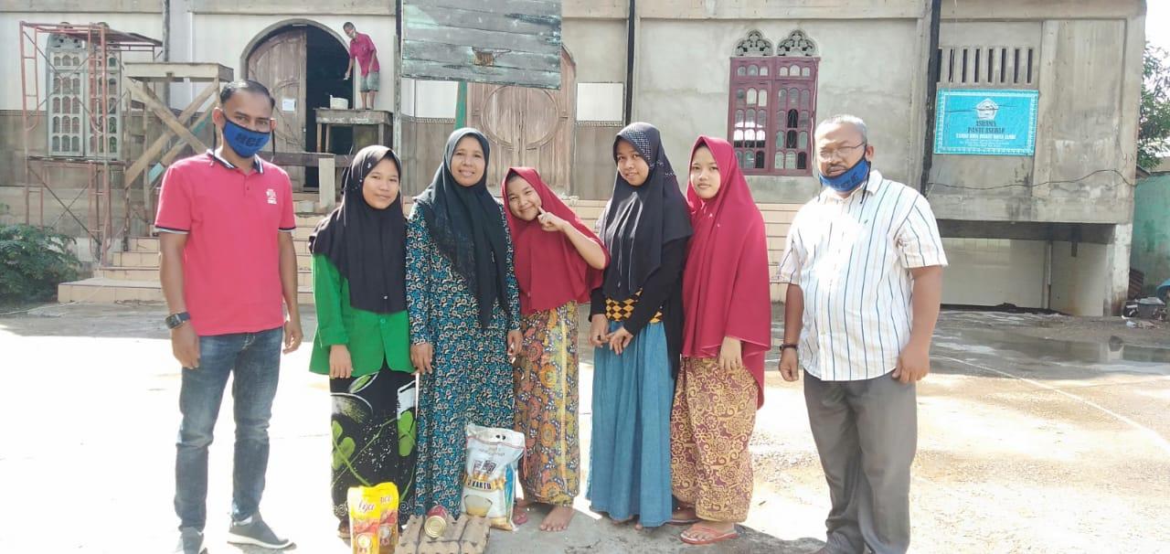 Anak-anak yatim piatu bina Insany menerima bantuan dari Cek Endra di depan sebuah masjid.