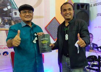 Kolonel Irman Putra SH MH menyerahkan bukunya kepada Wakil Walikota Dr Maulana di sela-sela syukuran KIRAPOTI Cafe dan Resto